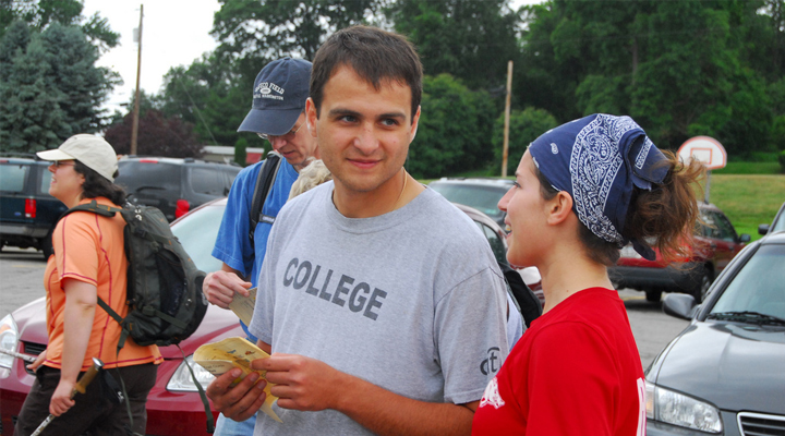 Young man wearing grey T-shirt talking to a young woman