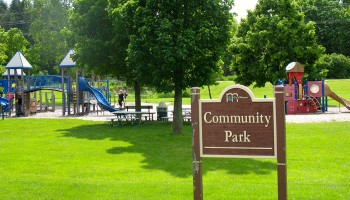 View of Mequon Community Park with trees, picnic tables and playground