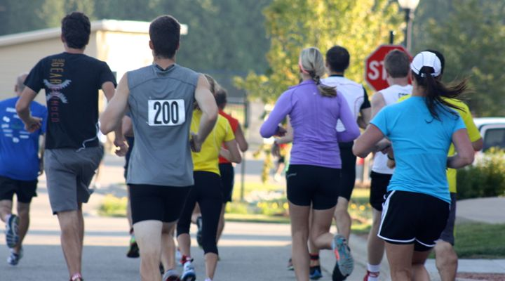 Backs of the competitors as they leave on the first 2.5 mile run
